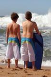 Jungen der hinteren Ansicht zwei, die auf dem Strand stehen Lizenzfreie Stockbilder