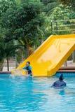 Jungen, die öffentlich Swimmingpool spielen lizenzfreie stockfotos