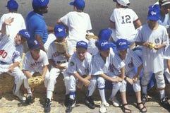 Jungen, die auf Bank sitzen Stockbild