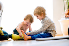 Jungen, die auf dem Boden spielt auf Tablette sitzen Lizenzfreie Stockbilder