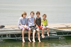 Jungen, die auf dem Dock sitzen Lizenzfreie Stockbilder