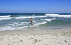 Jungen, die auf dem Strand spielen lizenzfreies stockfoto