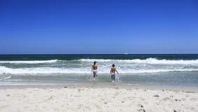 Jungen, die auf dem Strand spielen lizenzfreie stockfotografie