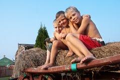 Jungen, die auf einem Heuballen auf Himmelhintergrund sitzen Lizenzfreies Stockbild