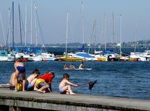 Jungen, die auf einem Pier fischen stockfotografie