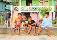 Jungen, die auf Geländern in Labuan Bajo sitzen Lizenzfreie Stockfotografie