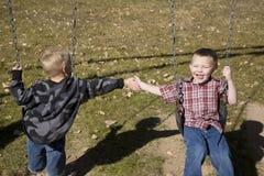 Jungen, die auf Schwingen spielen Lizenzfreies Stockfoto