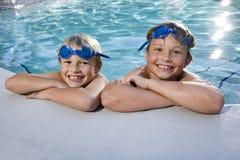 Jungen, die auf Seite des Swimmingpools grinsen stockfotografie