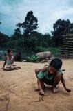 Jungen, die buddhistische Symbole und Kunst im Sand während große Durchläufe vorbei im Hintergrund zeichnen lizenzfreies stockbild