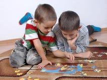 Jungen, die das Puzzlespiel spielen Stockfotos