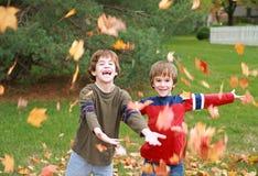 Jungen, die in den Blättern spielen lizenzfreies stockbild