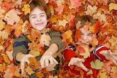 Jungen, die in den Blättern spielen Lizenzfreie Stockfotos