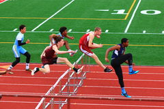 Jungen, die in den Hürden an einem Bahn-Wettbewerb konkurrieren stockfoto