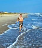 Jungen, die den schönen Ozean und den Strand genießen Stockbild