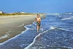 Jungen, die den schönen Ozean und den Strand genießen Stockfotografie