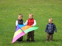 Jungen, die Drachen fliegen Stockbild