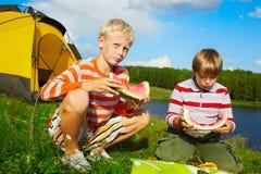 Jungen, die draußen Wassermelone essen Lizenzfreie Stockfotos