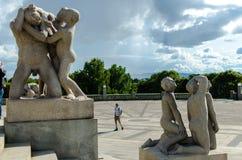 ` Jungen, die eine schwachsinnig Mann ` Skulptur bei Frogner necken, parken stockbilder