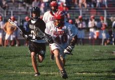Jungen, die in einem High School Lacrossespiel spielen lizenzfreies stockfoto