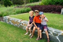 Jungen, die in einem Park sitzen Stockfotos