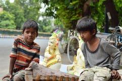 Jungen, die für ein Foto mit Lord Krishnas Statue aufwerfen Lizenzfreie Stockbilder