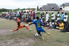 Jungen, die Fußball auf lokalem Feld mit Zuschauern herum spielen Lizenzfreie Stockfotos
