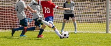Jungen, die Fu?ball spielen Jungen, die Fu?ball auf dem Sportfeld treten stockfotografie