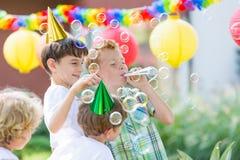Jungen, die Geburtstagshüte tragen lizenzfreies stockbild