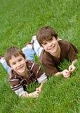 Jungen, die in Gras legen Stockfoto