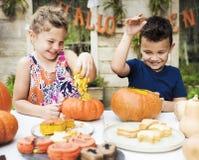 Jungen, die Halloween-Steckfassung-Olaternen schnitzen lizenzfreies stockfoto