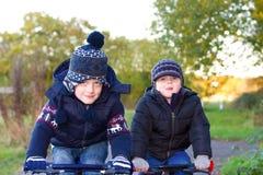 Jungen, die ihre Fahrräder in einem Landpark reiten stockfoto