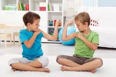 Jungen, die ihren Muskel vorführen Stockbild
