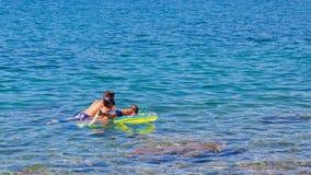 Jungen, die im sauberen blauen Meer schnorcheln lizenzfreies stockbild