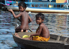 Jungen, die mit dem Boot im Tonle Sap See reisen Stockbild