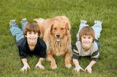 Jungen, die mit dem Hund legen Lizenzfreie Stockfotografie