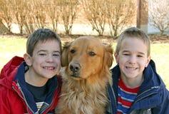 Jungen, die mit Hund lächeln Lizenzfreie Stockfotografie