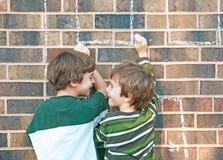 Jungen, die mit Kreide spielen Lizenzfreie Stockbilder