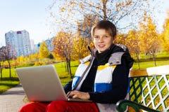 Jungen, die mit Laptop draußen lernen Stockfotografie