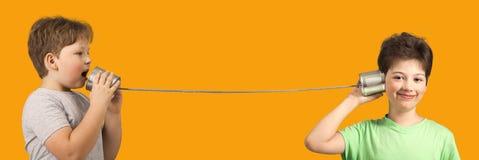 Jungen, die mit Tin Can Phone spielen Lokalisiert auf orange Hintergrund lizenzfreie stockfotos