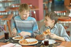 Jungen, die Pizza essen lizenzfreie stockfotos
