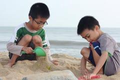 Jungen, die Sand-Schloss aufbauen Stockbild