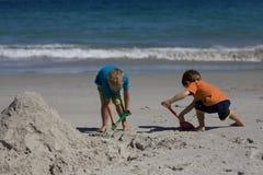 Jungen, die Sandschlösser auf dem Strand aufbauen Lizenzfreies Stockfoto
