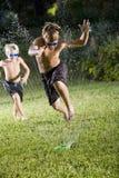 Jungen, die schnell durch Rasensprenger laufen Lizenzfreie Stockfotos