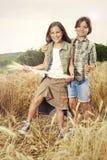 Jungen, die Spaß auf dem Weizengebiet haben stockfoto