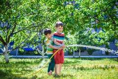 Jungen, die Spaß mit Bewässerungsfruchtgarten im Dorf draußen haben lizenzfreie stockfotos