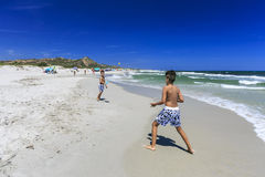 Jungen, die Tennis auf dem Strand spielen lizenzfreie stockfotos
