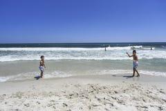 Jungen, die Tennis auf dem Strand spielen lizenzfreie stockfotografie