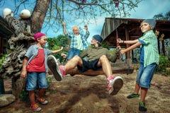 Jungen, die Vater auf Schwingen drücken Lizenzfreie Stockbilder