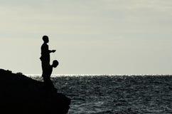 Jungen, die vom felsigen Ufer fischen Stockfoto