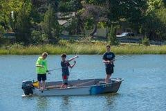 Jungen, die von einem Boot fischen Lizenzfreie Stockbilder